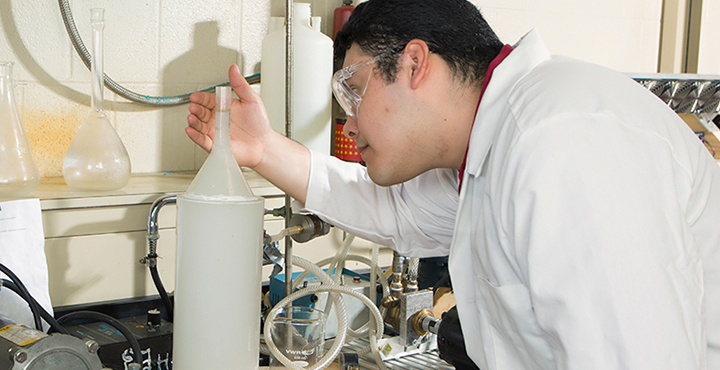 Student in lab coat and safety goggles checks on an experiment.
